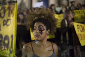 A woman wearing a female gender symbol attends a protest against the gang rape of a 16-year-old girl in Rio de Janeiro, Brazil, Friday, May 27, 2016. The assault last Saturday came to light after several men joked about the attack online, posting graphic photos and videos of the unconscious, naked teen on Twitter. (AP Photo/Leo Correa)